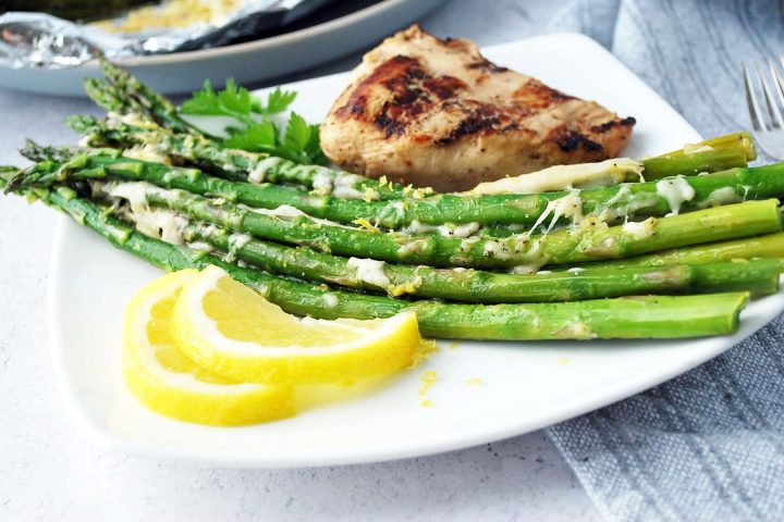 Grilled asparagus on a plate with lemon slices and grilled chicken