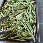Roasted green beans on a cookie sheet with tongs