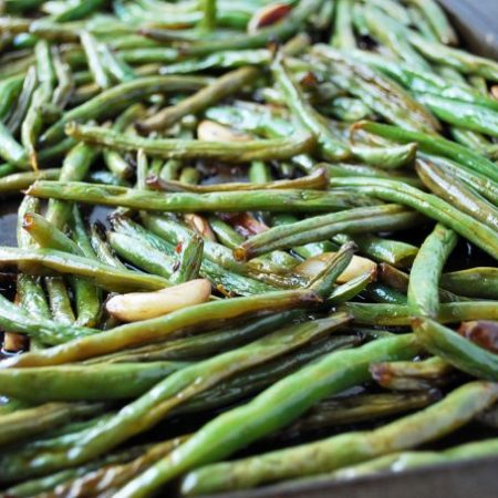 A close up of roasted green beans with garlic cloves