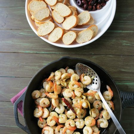 Cooked shrimp in a skillet with a spoon and a tray of olives and bread in the background