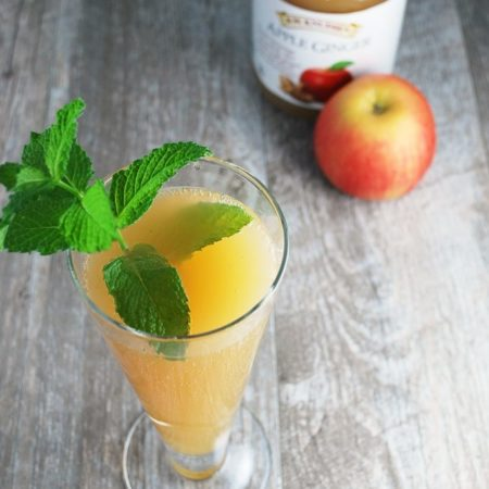 Apple drink with fresh mint with an apple in the background