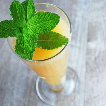 overhead photo of an apple sparkler drink with a sprig of mint