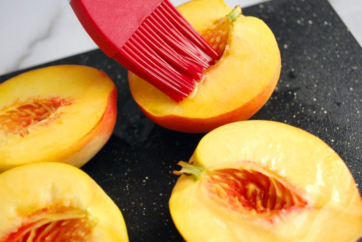 Fresh peach halves getting basted with olive oil
