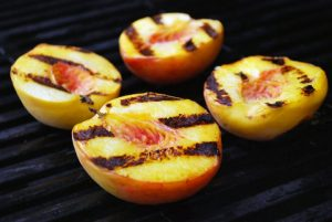 Fresh peaches cooked on a grill with grill marks