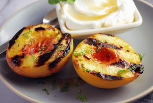 Grilled peach halves on a plate with fresh mint, maple syrup and yogurt