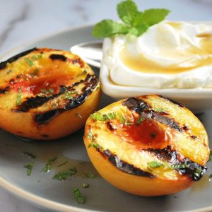 plate of grilled peaches with yogurt and mint