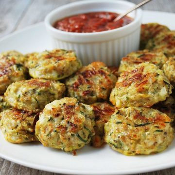 zucchini tots stacked on a white plate with a ramekin of pizza sauce on the side