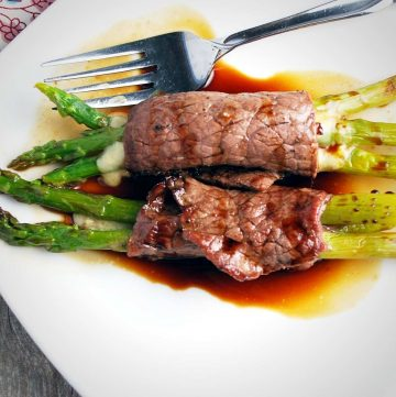 two beef asparagus bundles on a white plate drizzled in balsamic sauce
