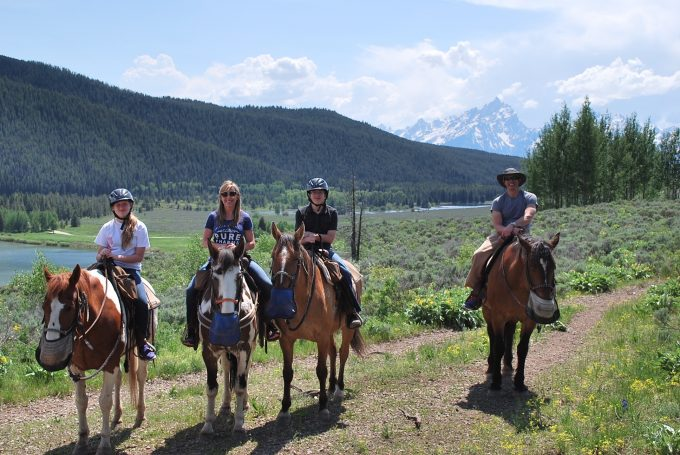 A group of people riding horseback with the Grand Tetons in the background