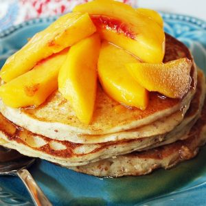 plate of gluten-free protein pancakes with fresh peaches on top