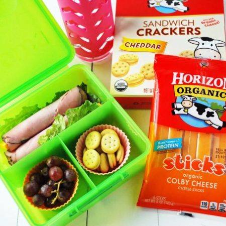 A green divided lunch box filled with ham roll-ups, grapes, and cheese sandwich crackers