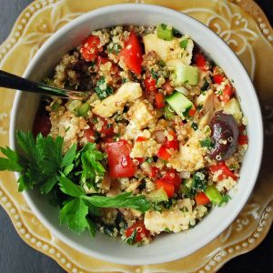 overhead photo of a chicken quinoa salad with fresh vegetables and olives and a sprig of parsley for garnish