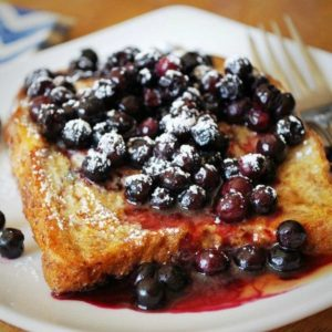 close up of whole grain French toast on a plate topped with wild blueberries and syrup with a fork on the side