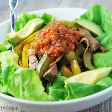 A bowl of Fajita salad with sliced avocados on top