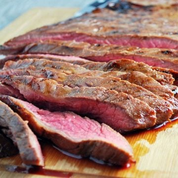 close up photo of a sliced flank steak on a cutting board
