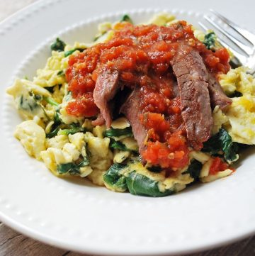 bowl of scrambled eggs with spinach topped with flank steak and salsa
