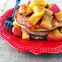 Pancakes topped with apples on a red plate