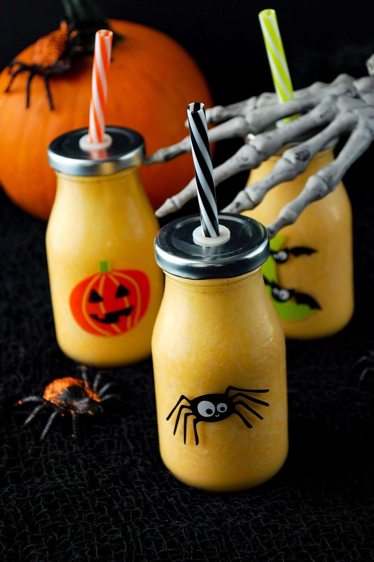 3 orange smoothies in Halloween themed glasses with a skeleton hand reaching out