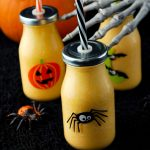 close up photo of halloween orange smoothies in Halloween glasses with lids and a straw