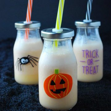 Three smoothies in small Halloween-themed glasses with straws