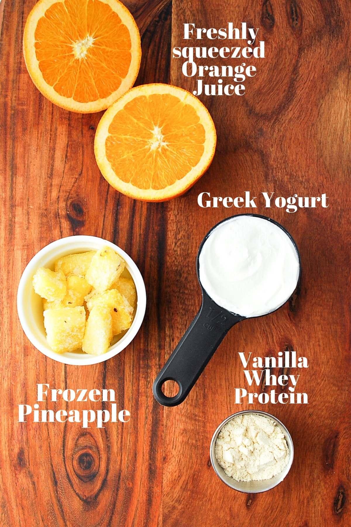 sliced orange, frozen pineapple, greek yogurt, and vanilla protein powder on a board for halloween smoothies