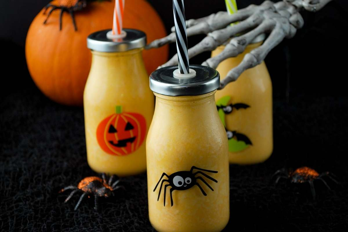 wide angle photo of orange healthy Halloween smoothies in Halloween jars with a pumpkin, fake spiders, and a skeleton hand