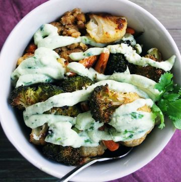 roasted broccoli, cauliflower, carrots, and grains in a bowl drizzled with a yogurt dressing and garnished with a sprig of parsley