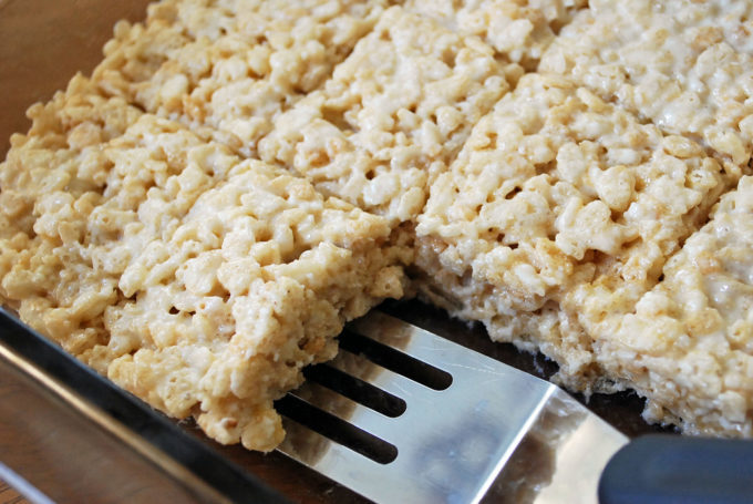 sheet pan with slices of protein rice crispy treats and spatula