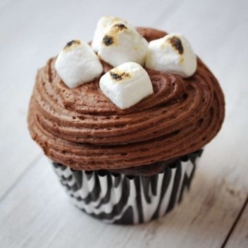 a chocolate frosted cupcake with roasted marshmallows on top