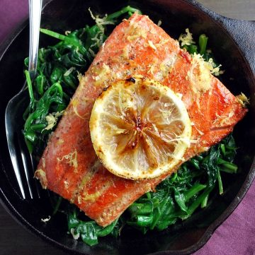 a salmon filet in a cast iron skillet over wilted spinach with a lemon slice on top