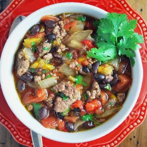 bowl of chili on a red plate with a sprig of fresh herbs