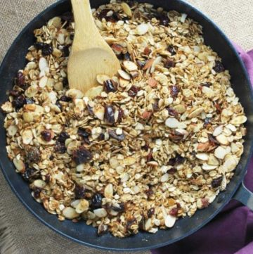 overhead photo of granola in a skillet with a wooden spoon