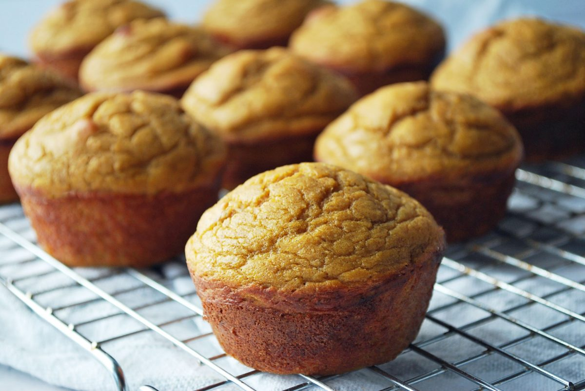 sweet potato muffins on a cooling rack with a napkin underneath