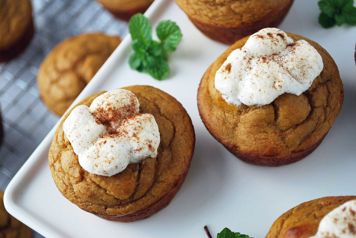 close up of marshmallow topped muffins on a platter with sprigs of fresh mint