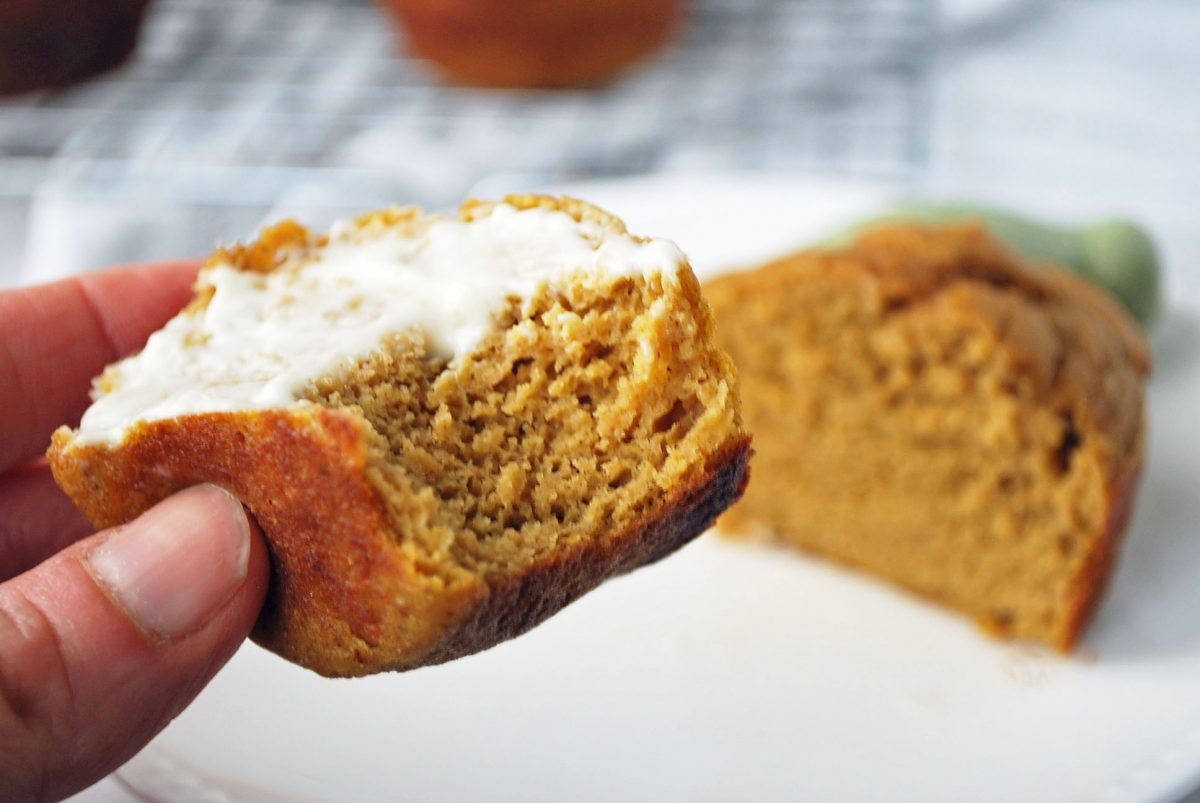 someone holding a half of a muffin topped with butter
