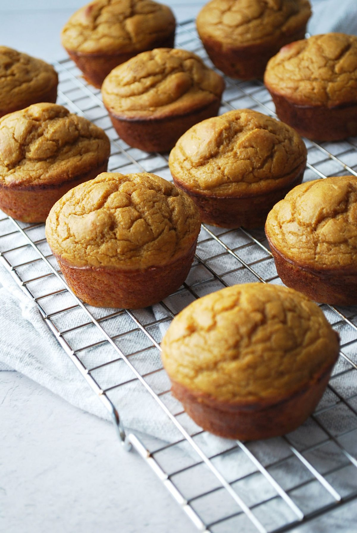 muffins on a cooling rack on top of a kitchen towel