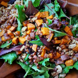 close up photo of sweet potato salad in a wooden serving bowl