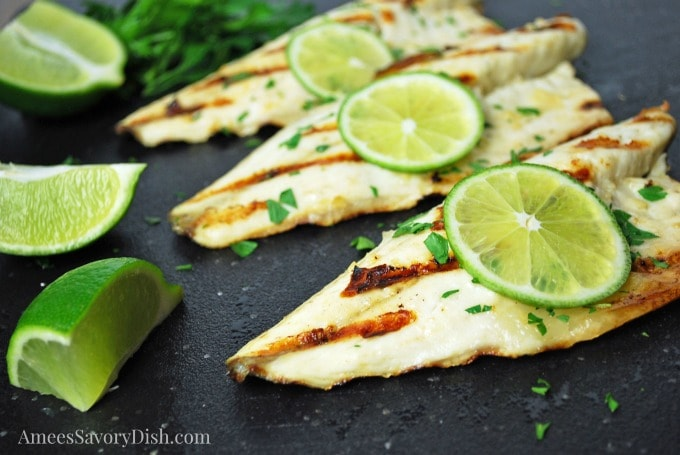 Sea Bass on a cutting board topped with fresh lime and herbs