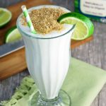 glass of key lime pie smoothie with graham cracker crumbs on top with straw