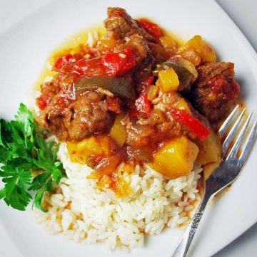 Cubed beef with peppers and mango over rice with a sprig of parsley on the side