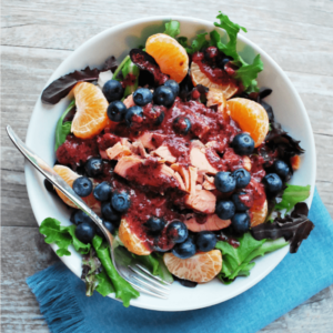 Blueberry and Salmon salad in a bowl with a blue napkin underneath