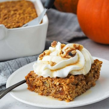 a square slice of pumpkin baked oats with whipped cream and nuts with a pumpkin in the background