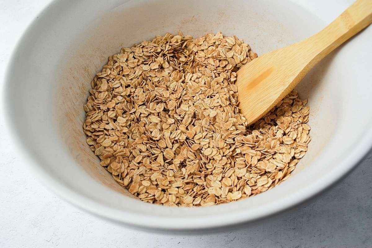 dry oats and spices mixed in a bowl with a wooden spoon