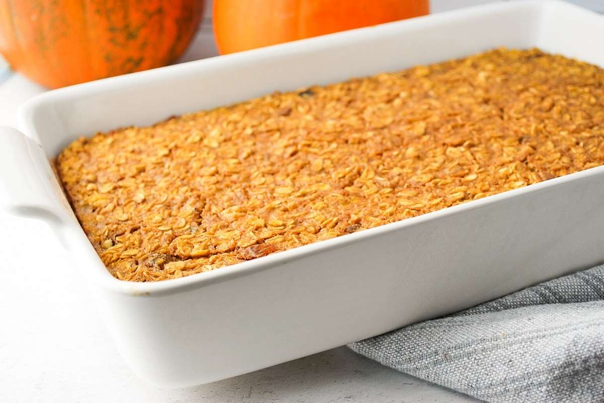 Freshly baked pumpkin pie oatmeal in a white baking dish with a towel underneath
