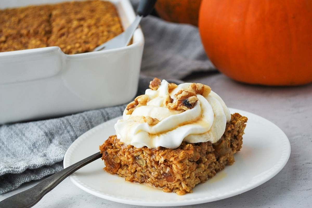 pan of pumpkin baked oats with a sliced pie on a white plate with a fork