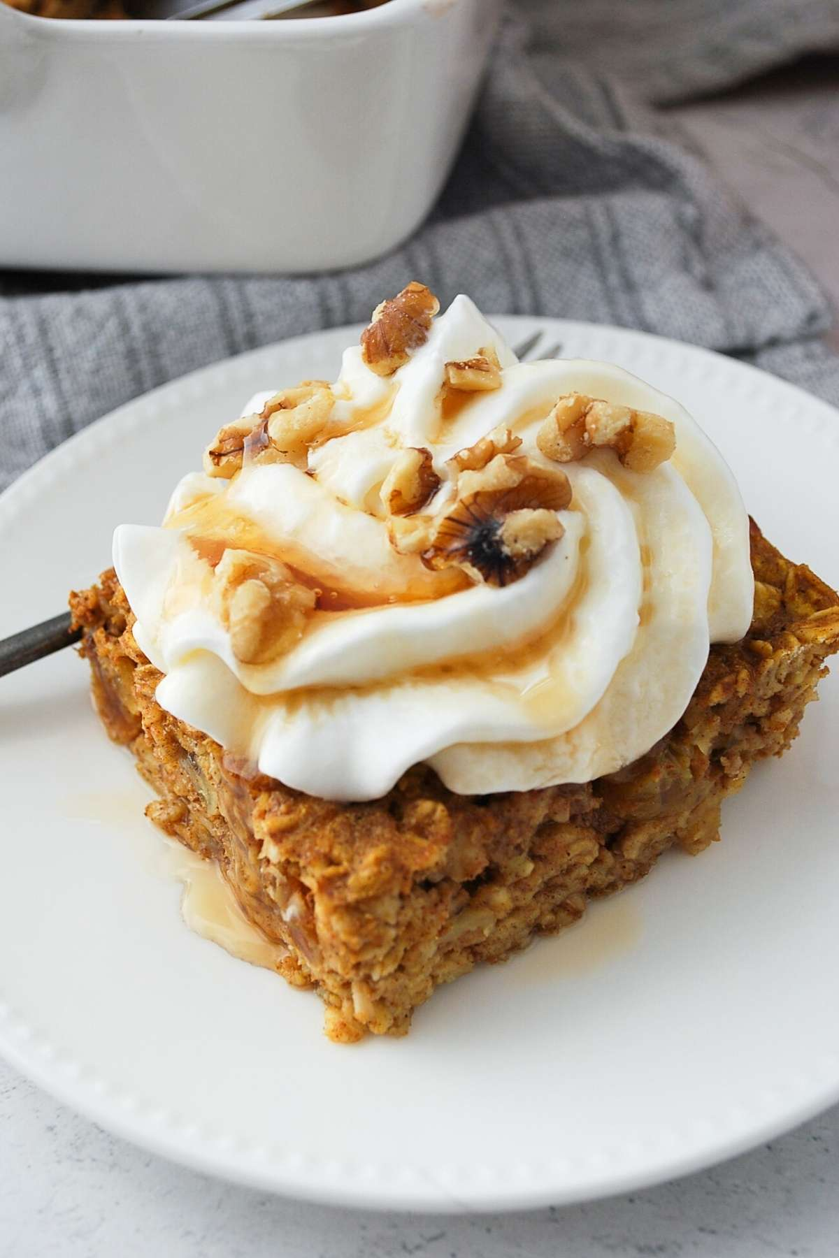 close up of a slice of pumpkin pie baked oatmeal with whipped cream, nuts, and syrup