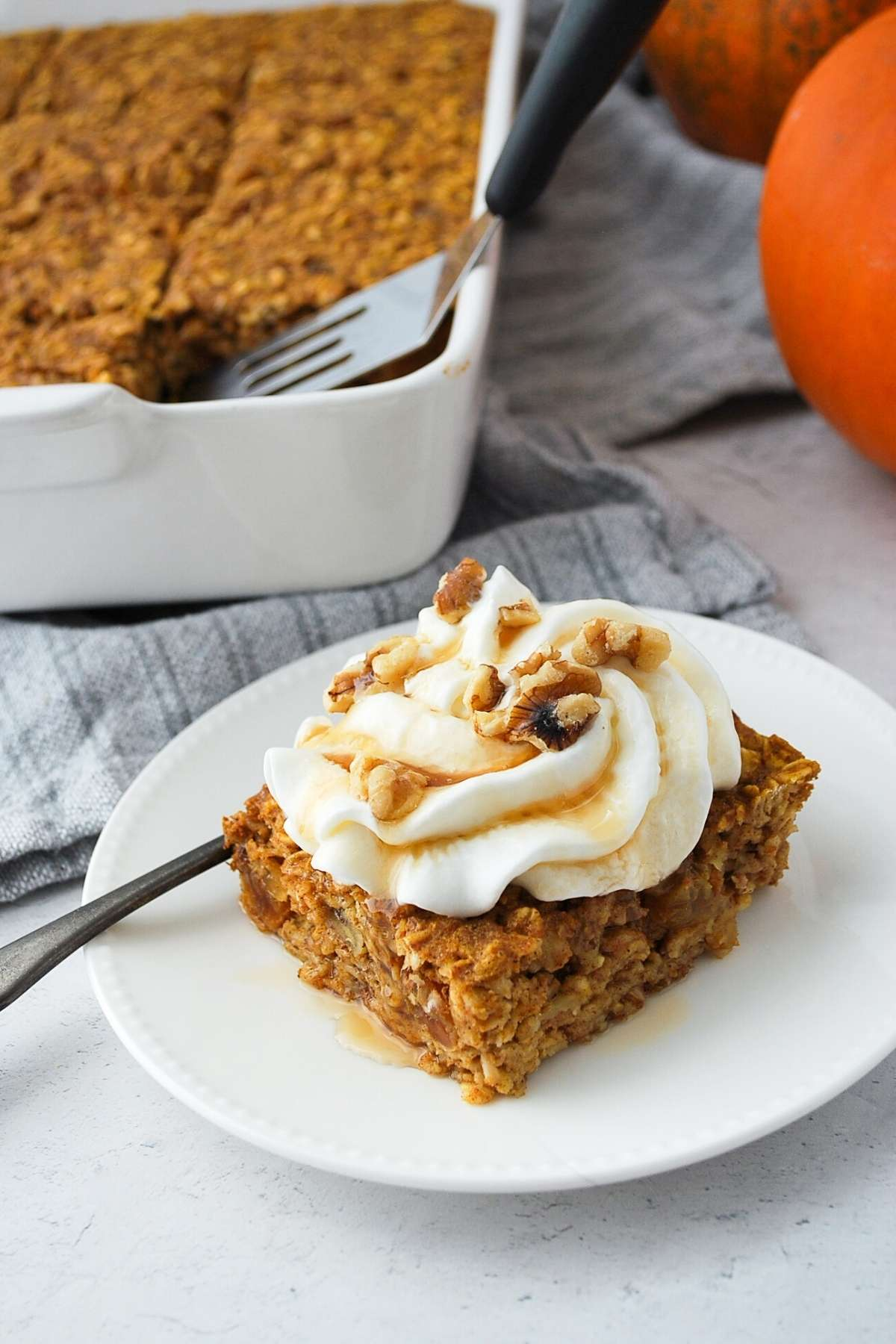 a slice of pumpkin baked oatmeal on a plate with whipped cream, nuts, and maple syrup on top with a pan of baked oats behind it