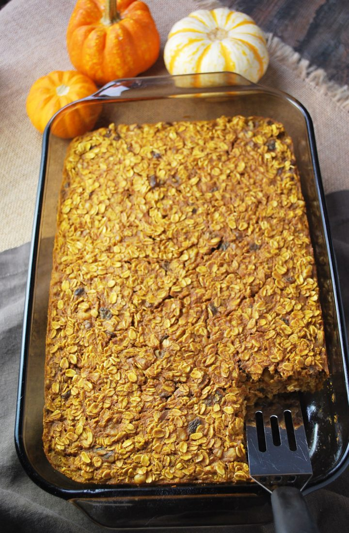 overhead shot of pan of pumpkin spice baked oatmeal with slice cut out