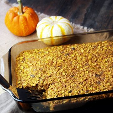 pan of pumpkin baked oatmeal with mini pumpkins in background