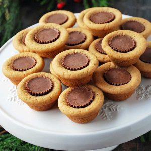 peanut butter cookie cups stuffed with a mini Reece's peanut butter cup stacked on a white platter